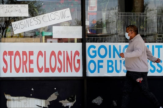A man looks at signs of a closed store due to COVID-19 in Niles, Ill. U.S.   (AP Photo/Nam Y. Huh, File)