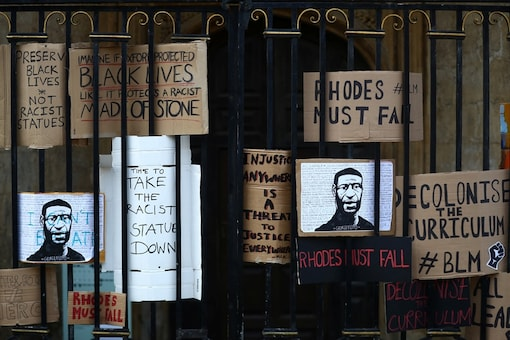 Placards in reference to the Black Lives Matter campaign are seen placed in the gates to Oriel College during a protest for the removal of a statue of British imperialist Cecil Rhodes on the outside of the college in Oxford. (REUTERS)