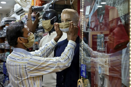 A worker adjusts a face mask on a mannequin in Kolkata. (Reuters)