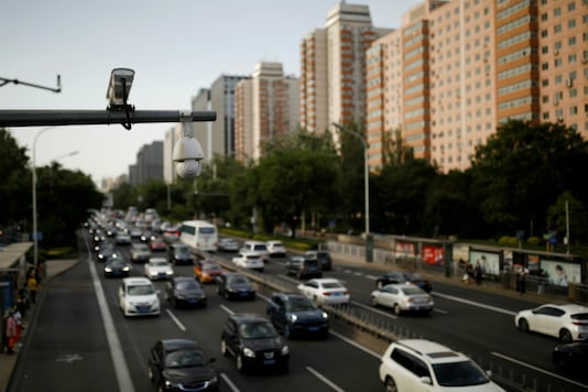 Surveillance cameras are seen above cars in the evening rush hour traffic at a road in Beijing, China. (Image Source: Reuters)