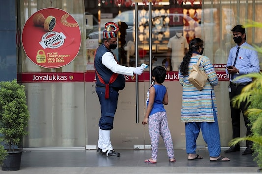 File photo of a security guard checking the temperature of a girl as a precaution outside a store in Bengaluru. (AP)