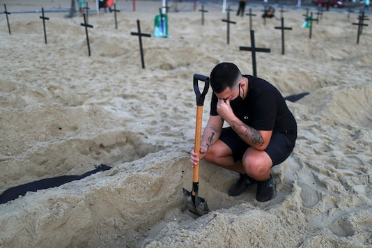An activist of the NGO Rio de Paz wearing a protective mask reacts as he attends a demonstration during which one hundred graves were dug on Copacabana beach symbolising the dead from COVID-19, in Rio de Janeiro, Brazil, June 11, 2020. (Image: REUTERS)