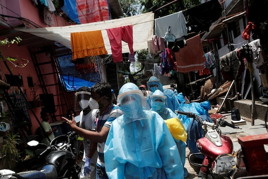 File photo of healthcare workers in personal PPEs and volunteers walking through a slum in Dharavi, Mumbai. (Reuters)