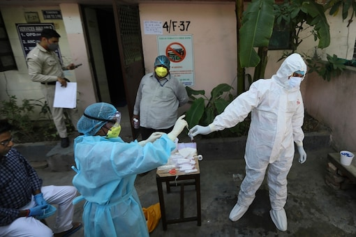 A health worker transfers sample of a person from a swab test for COVID 19 in New Delhi. (AP)
