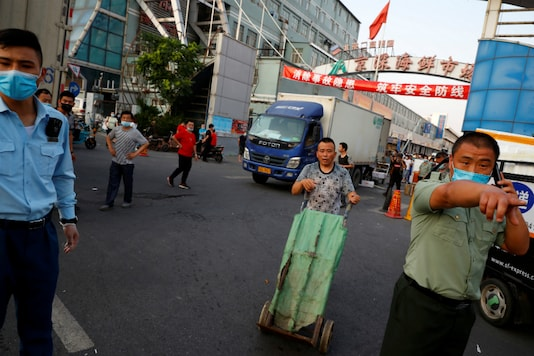Security guards wearing face masks stand outside the Jingshen seafood market which has been closed for business after new coronavirus infections were detected, in Beijing. (Reuters)