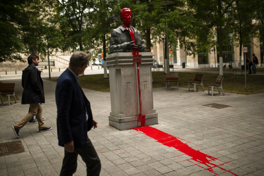 People walk past a bust of former Belgium's King Baudouin being vandalised and covered in red paint in Brussels. The red paint vandalism of the statue forms part of anti-racism protests in Brussels. (Image: AP)