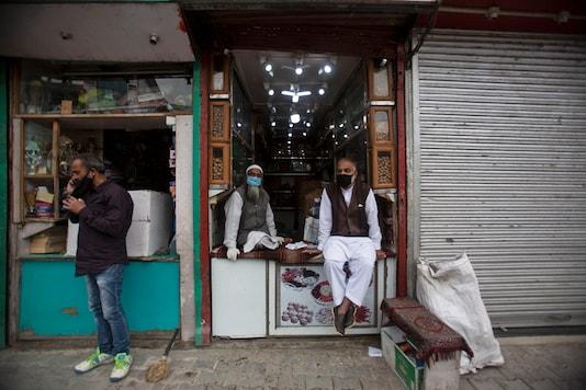 FILE PHOTO: Kashmiri shopkeepers wearing face masks wait for customers at a market in Srinagar, India, Saturday, June 13, 2020.  (AP Photo/Mukhtar Khan)