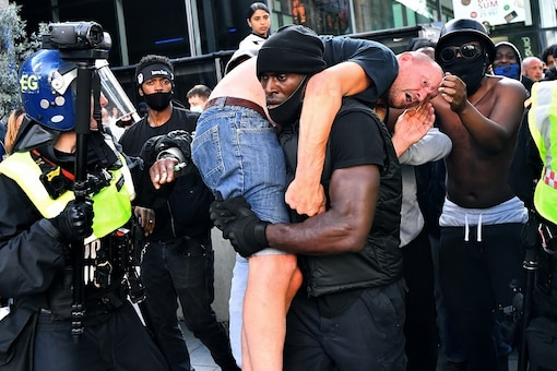Patrick Hutchinson, a protester, carries a suspected far-right counter-protester who was injured, to safety, near Waterloo station during a Black Lives Matter protest following the death of George Floyd in Minneapolis police custody, in London, Britain, June 13, 2020. REUTERS/Dylan Martinez