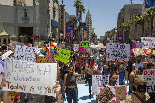 """People walk on Hollywood Boulevard for an """"All Black Lives Matter"""" march, organized by black members of the LGBTQ community, in the Hollywood section of Los Angeles. (Image: AP)"""