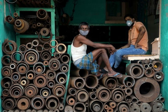Workers wearing face masks sit inside a shop in Kolkata. (Reuters)