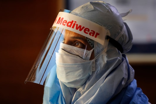 A health worker in protective suit listens to people standing in a queue for COVID 19 test at Sir Ganga Ram hospital in New Delhi, India, Tuesday, June 16, 2020. India is the fourth hardest-hit country by the COVID-19 pandemic in the world after the U.S., Russia and Brazil. (AP Photo/Manish Swarup)