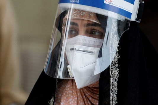 A woman wears a protective face shield and a protective face mask as she attends an event of mask distribution along a road, as the outbreak of the coronavirus disease (COVID-19) continues, in Karachi, Pakistan June 15, 2020. REUTERS/Akhtar Soomro