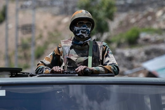 An Indian army soldier guards atop one of the vehicles as an army convoy moves on the Srinagar- Ladakh highway at Gagangeer. (AP Photo/Mukhtar Khan)