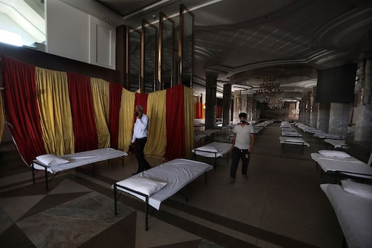 Workers walk across a banquet hall converted into a makeshift coronavirus hospital in New Delhi. (AP Photo/Manish Swarup)
