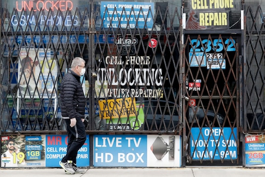In this April 30, 2020 file photo, a man walks by a closed store in Chicago. (AP Photo/Nam Y. Huh, File)