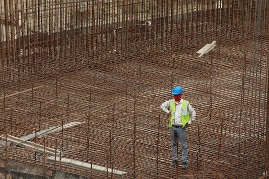 A labourer stands at a construction site after few restrictions were lifted by Delhi government, during an extended nationwide lockdown to slow the spread of the coronavirus disease (COVID-19) in New Delhi, India May 11, 2020. REUTERS/Anushree Fadnavis/File Photo