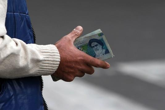 File photo of Iranian money changer with a wad of Iranian notes with Ayatollah Ruhollah Khomeini's image in Tehran. (AP Photo/Hasan Sarbakhshian, File)