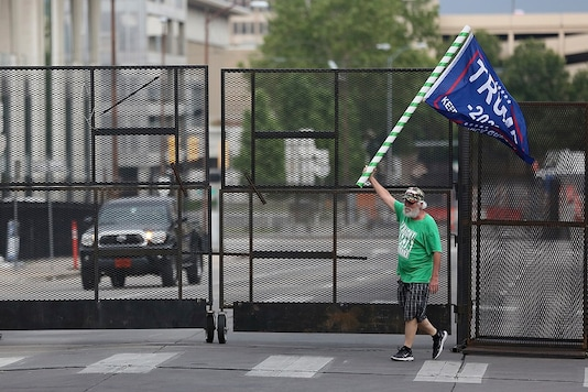 A man waves a Donald Trump campaign flag near a barricade in downtown Tulsa, Oklahama ahead of the president's rally on Saturday. (Reuters)