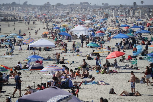 In this May 24, 2020, file photo, visitors gather on the beach in Newport Beach, California, during the coronavirus outbreak. (AP Photo/Marcio Jose Sanchez, File)