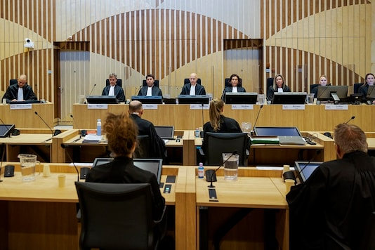 File photo of presiding judge Hendrik Steenhuis, rear, fourth from left, opens the court session as the trial. (AP Photo/Robin van Lonkhuijsen, Pool, File)