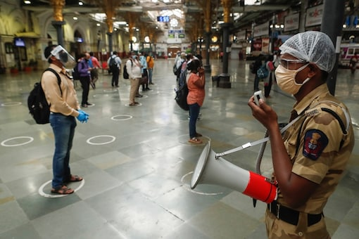 For representation: A railway police official makes an announcement on a loudspeaker telling commuters to stand inside the designated circles to maintain social distancing as they wait to board a train at a railway station after some restrictions were lifted during a lockdown to slow the spread of the coronavirus disease (COVID-19) in Mumbai, India, June 22, 2020. (Image: REUTERS)