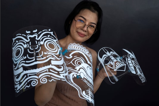 Maysa Talerd, 31, an entrepreneur, holds up her own designs for face shields, as she poses during an interview with Reuters amid the spread of the coronavirus (COVID-19) disease in Bangkok, Thailand
