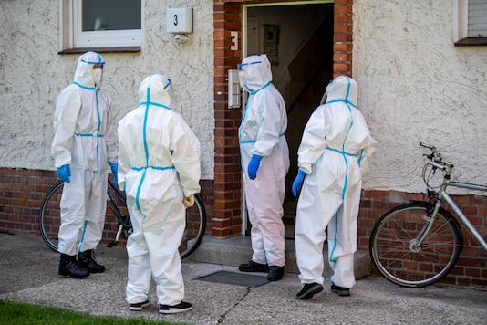 Members of German Red Cross (DRK) stand in front of a house where employees of the Toennies meat factory live in Rheda-Wiedenbrueck, Germany, Monday, June 22, 2020. About 40 mobile test teams are on the road that day to visit employees of the Toennies company at home in their quarantine. Hundreds of new coronavirus cases are linked to the large meatpacking plant, officials ordered the closure of the slaughterhouse, as well as isolation and tests for everyone else who had worked at the Toennies site — putting about 7,000 people under quarantiner. (David Inderlied/dpa via AP)
