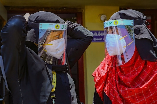 Bengaluru civic body's health workers adjust their face shields before entering the areas of Padarayanapura in Chamarajapet during ongoing Covid-19 crisis. (PTI)