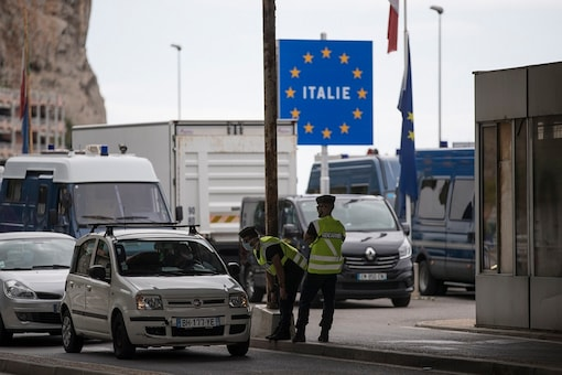 French gendarmes approach a car at the Saint-Ludovic border check point on the Franco-Italian border in Menton, France. (AP Photo/Daniel Cole)