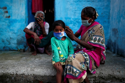 A woman adjusts her daughter's face mask in Delhi. (Reuters)