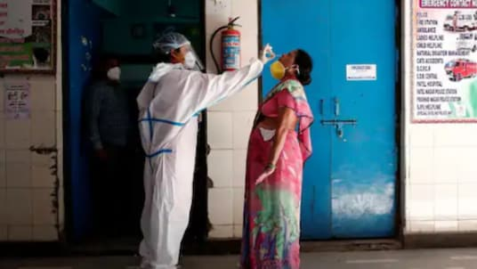 A medical worker collects a sample from a woman at a school turned into a centre to conduct tests for the coronavirus disease (COVID-19), amidst its spread in New Delhi on Monday. (Reuters)
