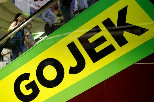 Commuters pass by a Gojek advertisement in Singapore. (Image Source: Reuters)