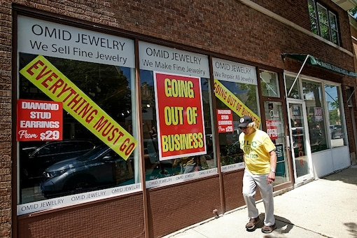 A man walks past a retail store that is going out of business due to the coronavirus pandemic in Winnetka, Illinois. (AP Photo/Nam Y. Huh)