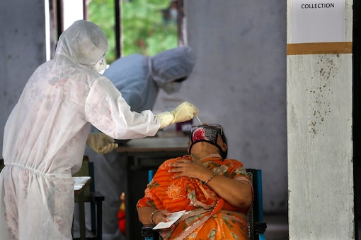 A health worker takes a nasal sample of a woman for the COVID-19 rapid antigen test in New Delhi. (AP)