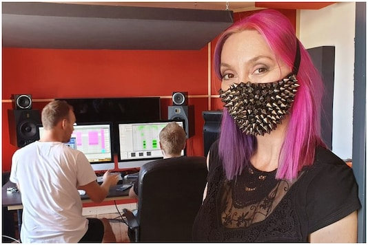 Belgian pop star Dana Rexx poses with a mask inside a studio | Image credit: Reuters