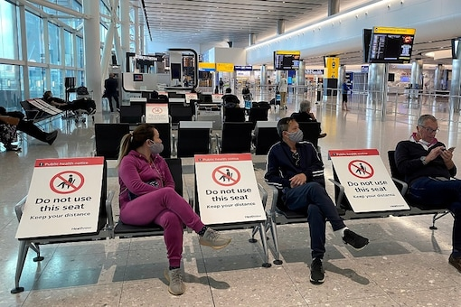 FILE PHOTO: People sit amongst socially-distanced seating signs at Heathrow Airport, as the spread of the coronavirus disease (COVID-19) continues, in London.   REUTERS/Toby Melville