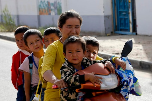 FILE - In this Sept. 20, 2018 file photo, a Uighur woman and children sit on a motor-tricycle after school at the Unity New Village in Hotan, in western China's Xinjiang region. Birth rates in the mostly Uighur regions of Hotan and Kashgar have plunged by more than 60% since 2015, government statistics show. (AP Photo/Andy Wong)