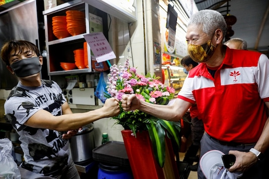 Lee Hsien Yang of the Progress Singapore Party (PSP) greets a hawker during a walkabout ahead of the general election in Singapore June 28, 2020.   REUTERS/Edgar Su