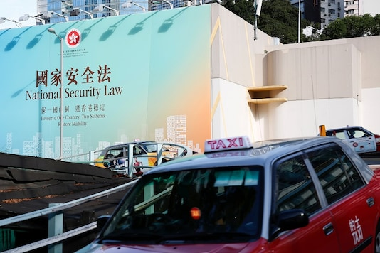 Taxis drive past government-sponsored advertisement promoting the new national security law during a meeting on national security legislation, in Hong Kong, China June 29, 2020. REUTERS/Tyrone Siu