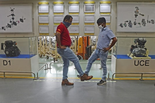 Workers greet each others by tapping their legs at an assembly unit of Royal Enfield motorcycle inside its factory after the government eased a nationwide lockdown imposed as a preventive measure against the COVID-19 coronavirus, in Oragadam, Tamil Nadu. (Image: AFP)