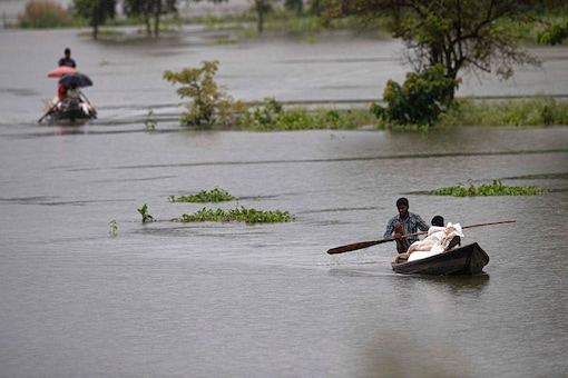 Villagers row country boats with their luggage to move to safer areas through floodwaters (AP)