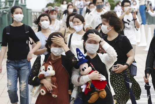 People wearing face masks to protect against the spread of the new coronavirus walk toward the entrance to Tokyo Disneyland in Urayasu, near Tokyo. (Image: AP)