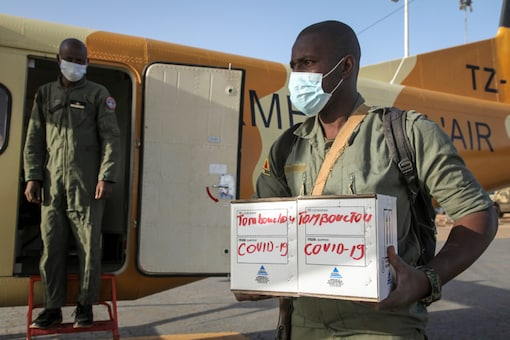 In this photo taken Friday, May 22, 2020, a Malian soldier in the capital Bamako, in Timbuktu, Mali, carries samples from patients in Timbuktu to a military plane flying them to be tested for the coronavirus. COVID-19 has made its way to Timbuktu, a town whose name has long been synonymous around the world with remoteness. (AP Photo/Baba Ahmed)