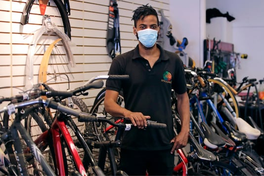In this Wednesday, June 24, 2020, photograph, Noah Hicks, owner of Spokehouse Bikes in the Upham's Corner neighborhood of Boston, poses at his shop. Many from outside Boston have donated to and shopped at the store which was robbed and vandalized earlier in the month. (AP Photo/Charles Krupa)