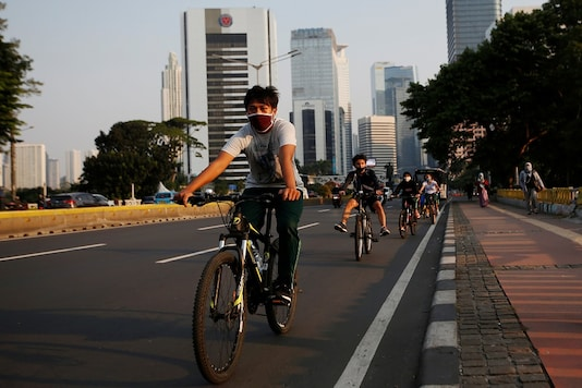 Youths ride bicycles on the main road after the government eased restriction measures following the coronavirus disease (COVID-19) outbreak in Jakarta, Indonesia. (Reuters)