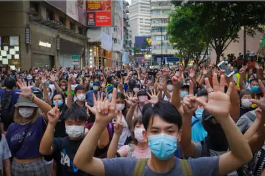 "Protesters against the new national security law gesture with five fingers, signifying the ""Five demands - not one less"" on the anniversary of Hong Kong's handover to China from Britain in Hong Kong. (Image: AP)"