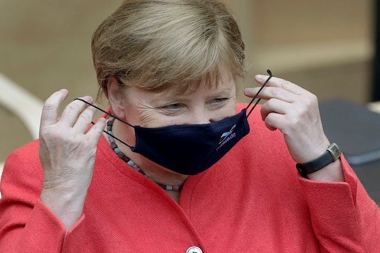 German Chancellor Angela Merkel adjusts her face mask as she arrives for a meeting of the upper house of the German legislative in Berlin on Friday. (AP)