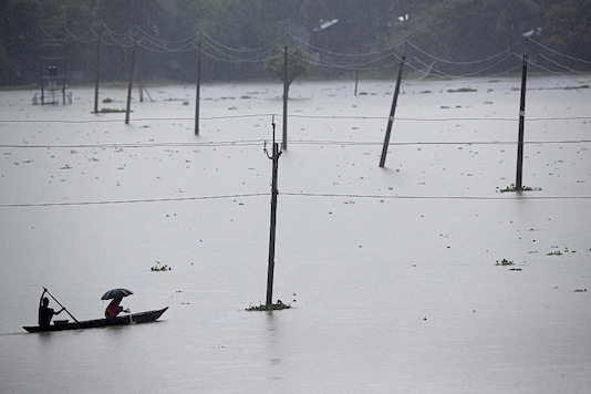 Villagers cross floodwaters on a country boat in Morigaon district of Assam. (AP Photo/Anupam Nath)
