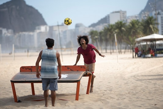 Two men play teqball amid the new coronavirus pandemic on Copacabana beach in Rio de Janeiro, Brazil. Authorities have begun to ease the city's lockdown amid the growing COVID-19 pandemic. (AP)