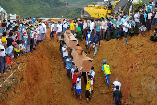 Volunteers carry coffins containing bodies of victims following a landslide at a mining site in Hpakant, Kachin State City, Myanmar July 3, 2020. REUTERS/Stringer